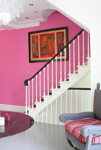 White staircase with one feature wall in bright pink, that has an abstract print hung on the wall