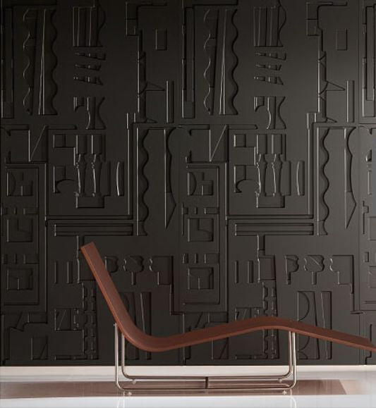 Embossed black wall that resembles Egyptian tomb art, with a brown chair in the foreground