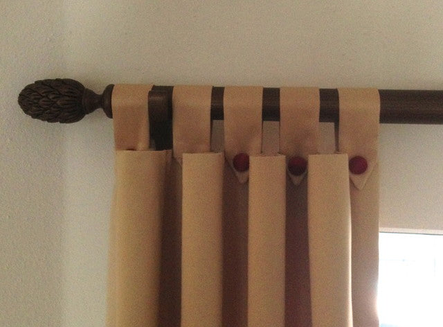 A wooden curtain pole with beige curtains hung at the pole, with looped hoops at the top tied to the curtain using buttons