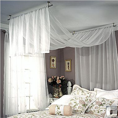 White and beige double bedding with a white voile bed canopy