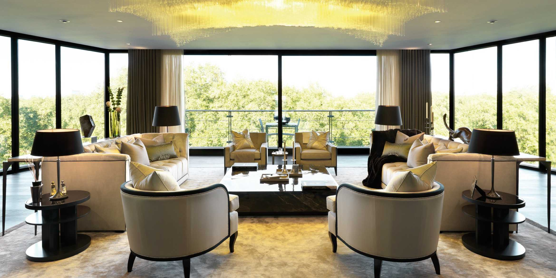 Floor to ceiling windows surround this living space with cream sofas with a black trim facing each other and a coffee table in the middle of the room