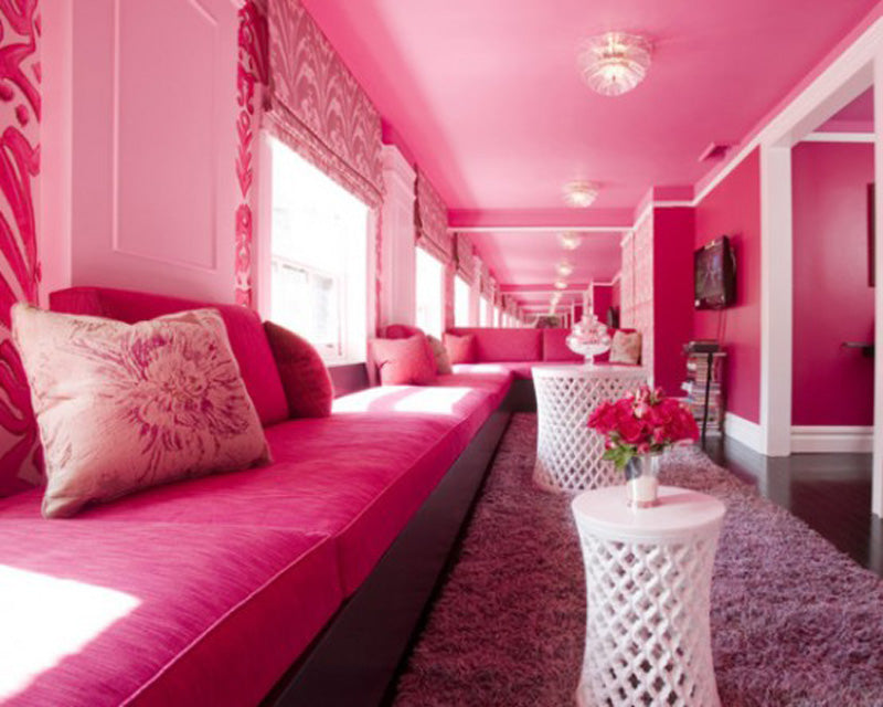 Vibrant pink long living room seats, with round white coffee tables and a mirror on either side of the room