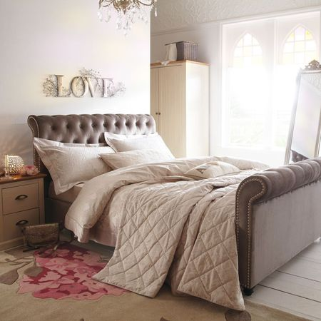 Beige sleigh bed with fabric headboard and raised footer, with cosy cream bedding