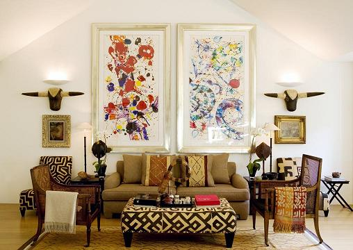 Light brown sofa under two abstract art prints on a white wall