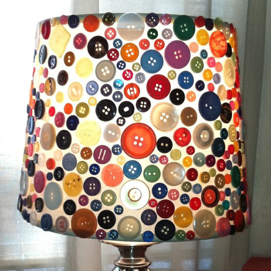 A white lampshade covered in lots of different coloured buttons
