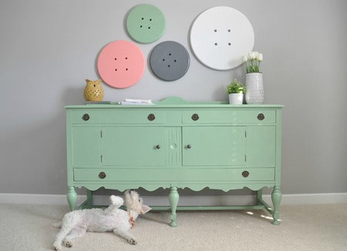 A light green dressing unit in front of a light grey wall with pastel toned button decorations on the wall
