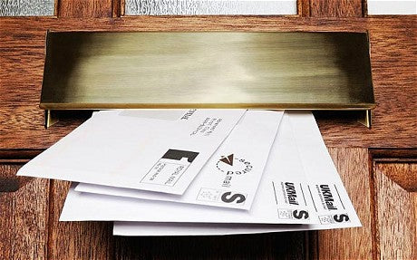 Four letters coming through a letterbox on a wooden door