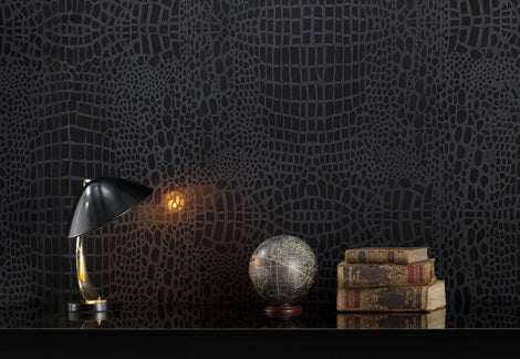 Textured black wall, with a table and lamp in the foreground