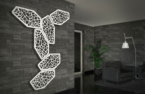 Six white irregular hexagonal fractal panels used as wall art on a grey tile wall