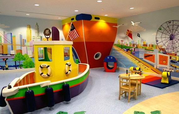 Fun kids bedroom with large tug boat in the middle of the room and cruise liner wall art in the corner