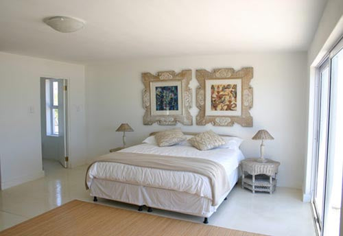 A white, cream and beige bedroom with french doors letting in light
