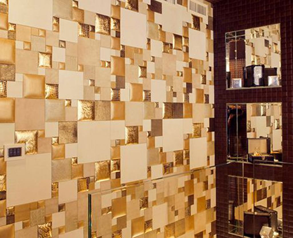 Different styled and sized gold tiles on a bathroom wall