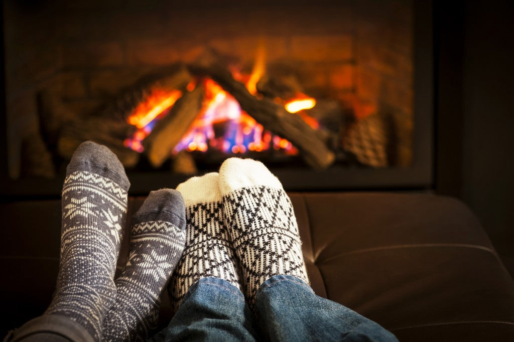 Two pairs of feet wearing cosy socks in front of a roaring log fire