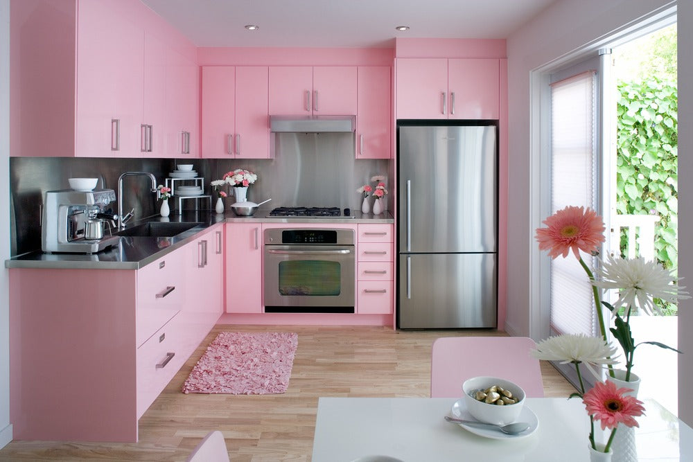 Soft pink kitchen units, with metal counters and appliances with sliding door into the garden