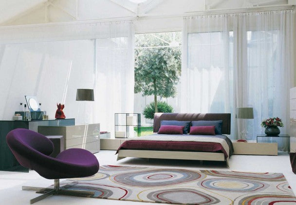 Fresh and spacious bedroom with large french doors covered in voile panels and a bed with maroon, blue and cream bedding