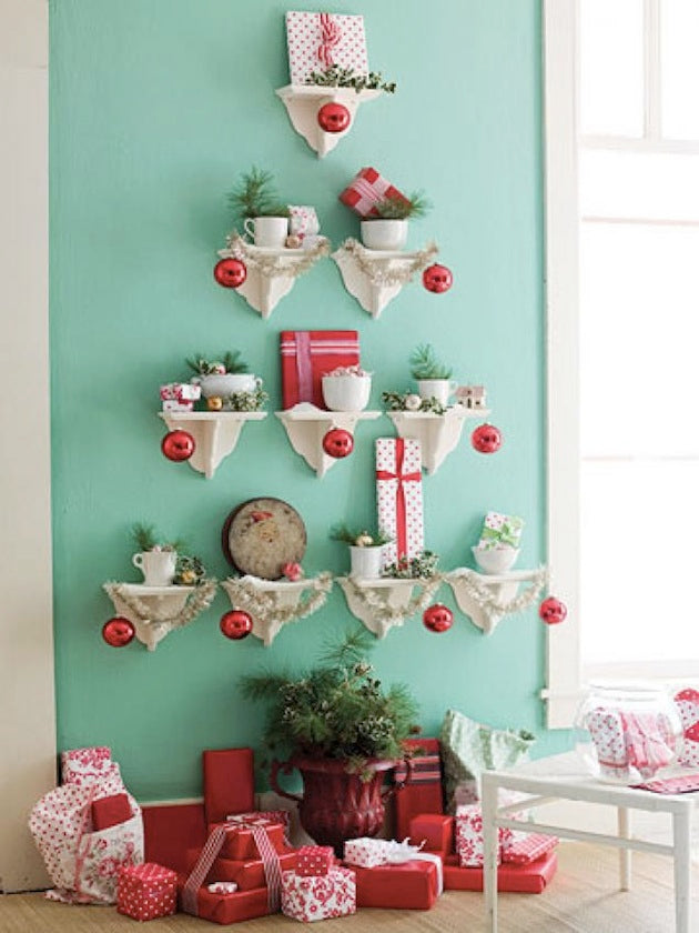 A light green living room wall with small white shelves arranged in the shape of a Christmas tree