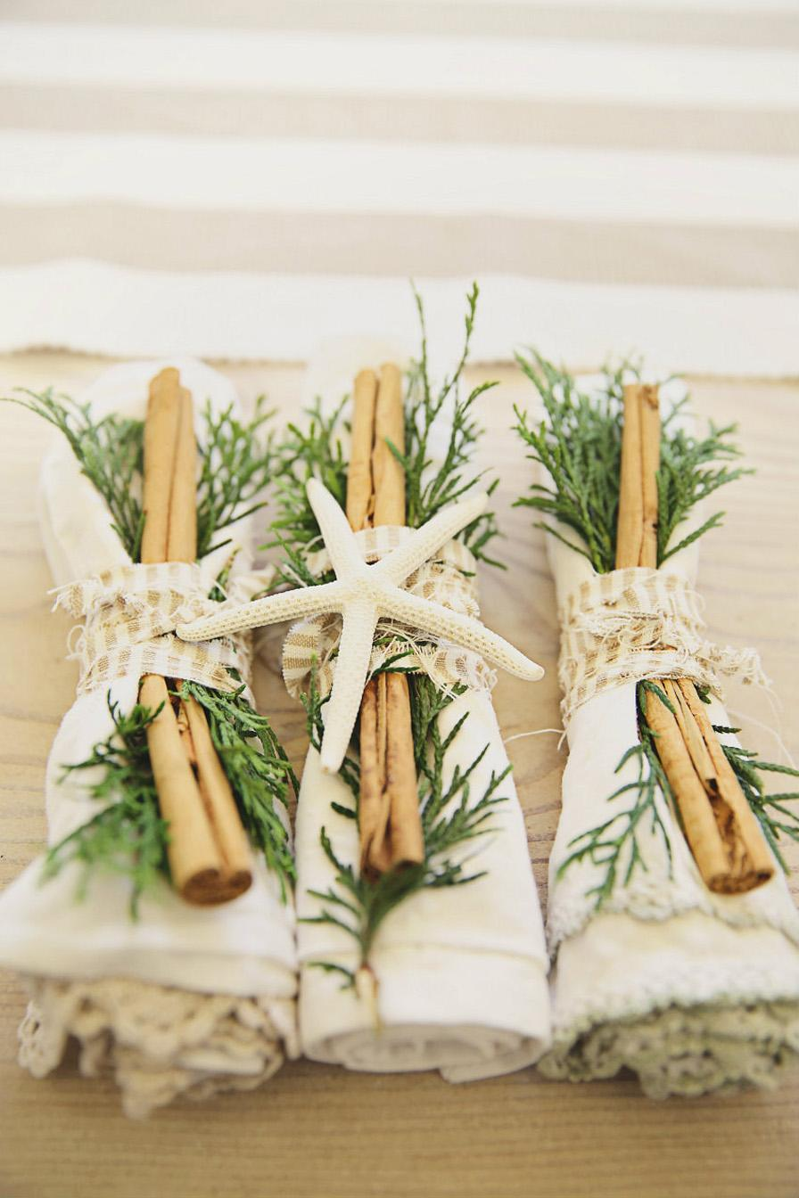 Three napkin table settings decorated with grass and a dried starfish