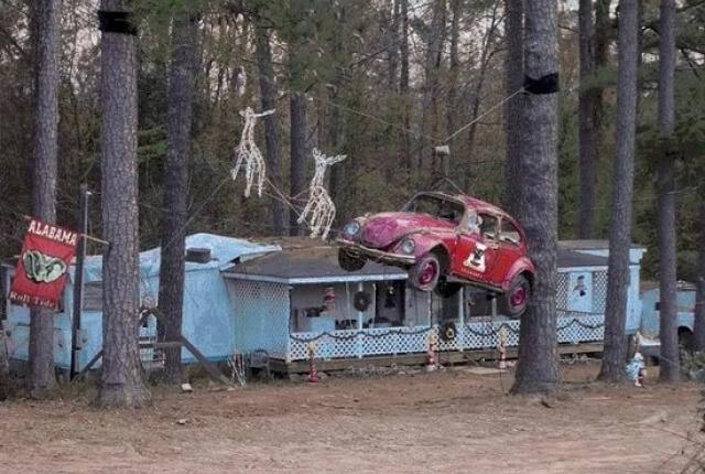 A VW Beetle car suspended by a wire between two trees, then two reindeer decorations have been suspended too as if they are pulling it