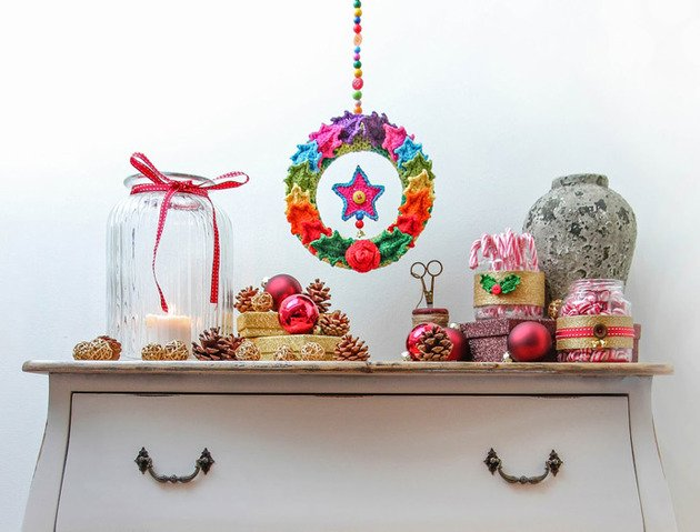 Wooden drawers with colourful Christmas decorations on the top, and a colourful wreath hung above