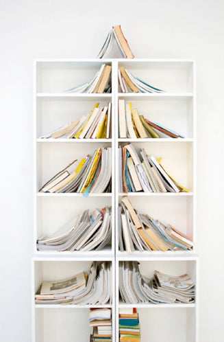 Tall bookshelves in two columns with books leaning inwards to form the shape of a Christmas tree