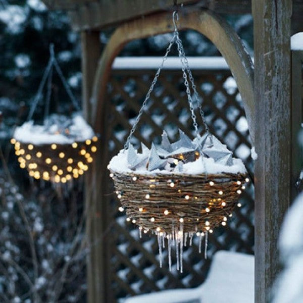 Wicker hanging baskets decoated with fairy lights and covered in snow