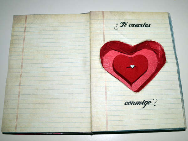 A hollowed out notepad, with a heart shaped hole decorated red and containing an engagement ring