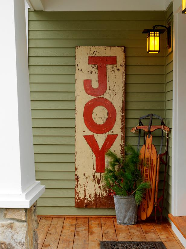 Sage green front porch, with a wooden decorative sign with the word Joy on it in red