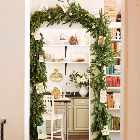 A tree garland archway over a door frame to the kitchen
