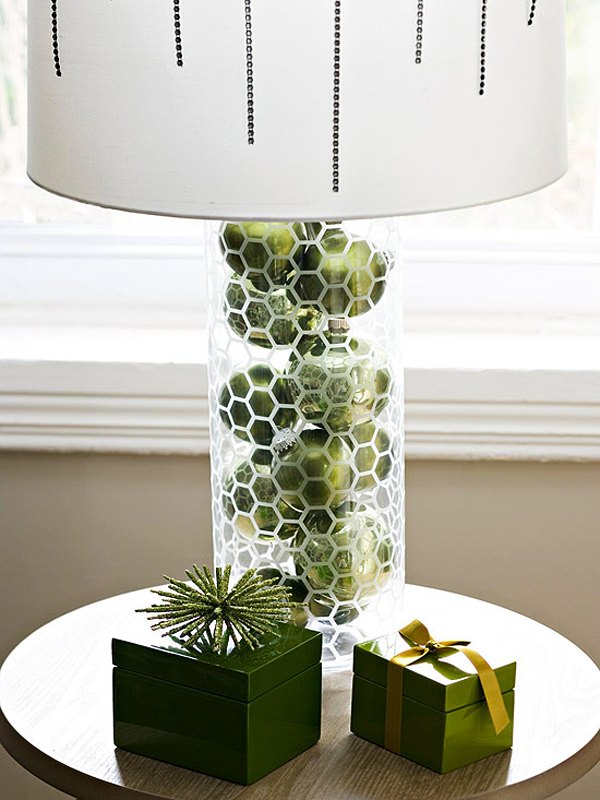 Glass cylinder lamp filled with green baubles and white lampshade