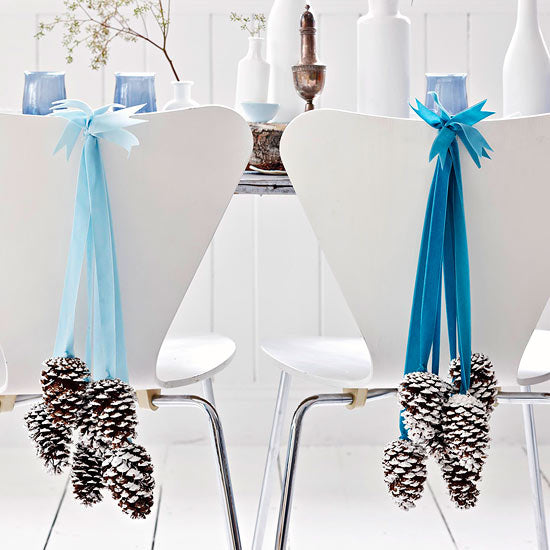 Blue voile and ribbon decorations with frosty pine cones hanging, on the back of white chairs