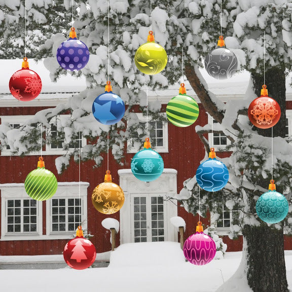 Coloured baubles hanging from a snow covered tree