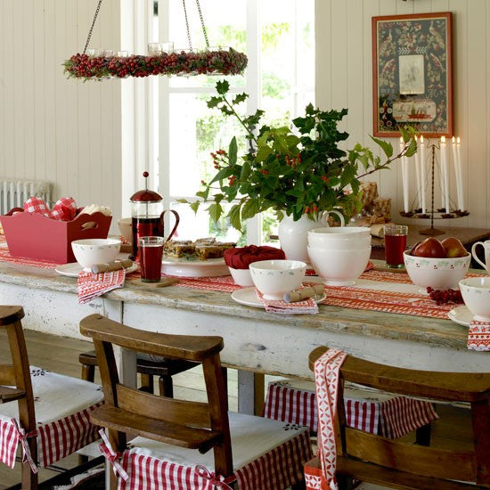 Lovely breakfast table with rustic wooden table and chairs, covered in red and white table cloth and cranberry wreath suspended above the table
