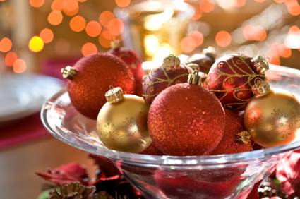 Orange and gold Christmas baubles in a glass bowl