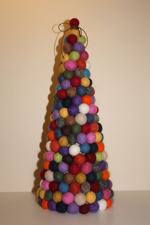 A Christmas tree made from tightly wrapped balls of wool in different colours