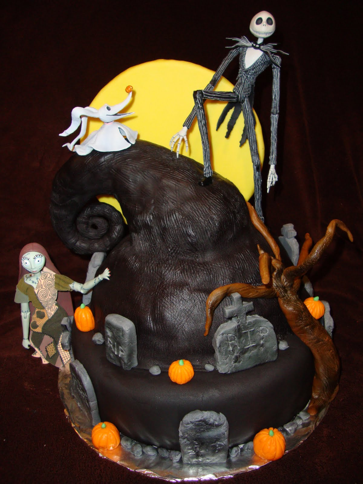 A cake made to look like a scene from A Nightmare Before Christmas, with Jack, Sally and Zero the ghost dog