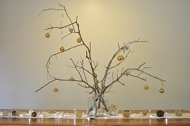 A decorative branch display using ornate baubles and Christmas lights