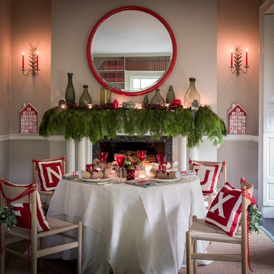 Festive dining room with green foliage over the mantel piece and red decorations throughout