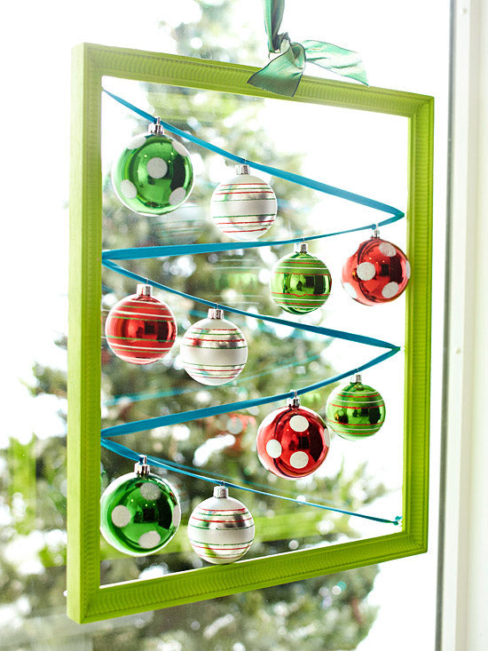 Green picture frame, with blue ribbon zigzagging inside it and baubles hanging from the ribbon