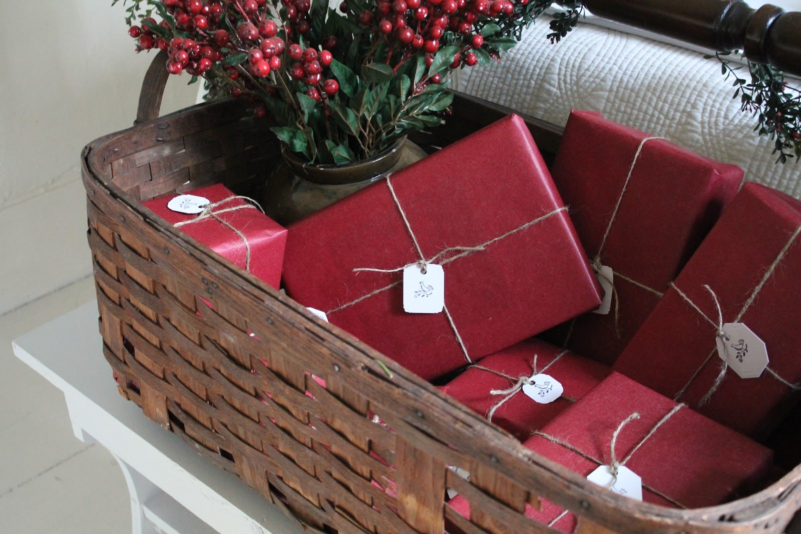 Dark wicker basket containing presents in red wrapping paper and a jar of cranberry branches