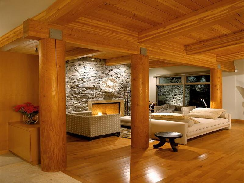 Light wood floors, ceiling and support beams in what looks like a basement living room