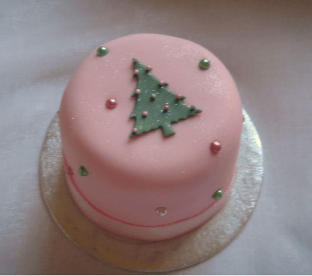 Light pink cake with a green icing Christmas tree on the top
