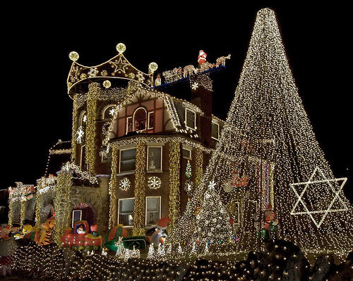 A house elegantly covered in bright white and gold Christmas lights