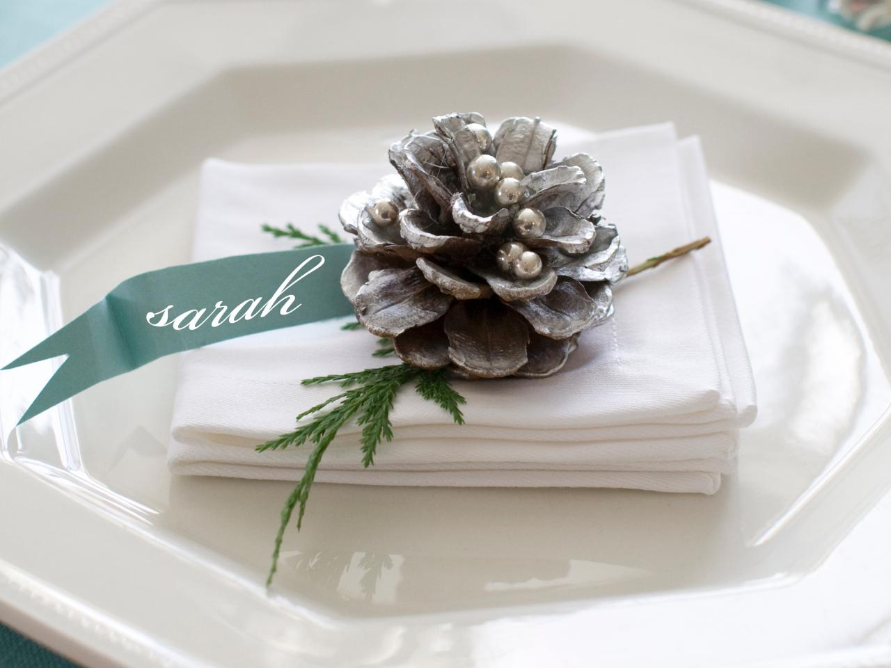 A place setting with napkin on a plate and then a silver pine cone on top