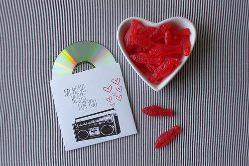 A ceramic heart bowl containing red sweets and a mixed CD tape