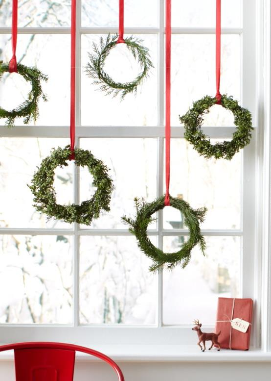 Wreathes hung from red ribbon in a white window frame