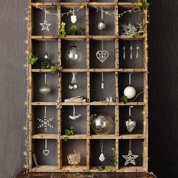 A wooden pigeon hole unit with Christmas decorations in each slot, and fairy lights around the outside