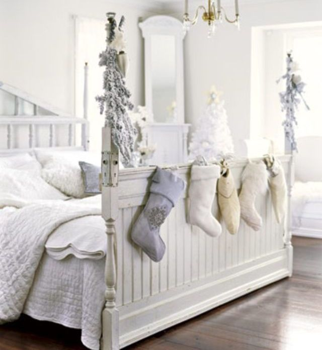 All white bedroom with stocking hung at the foot of the bed and decorative frosted branches on the bed frame
