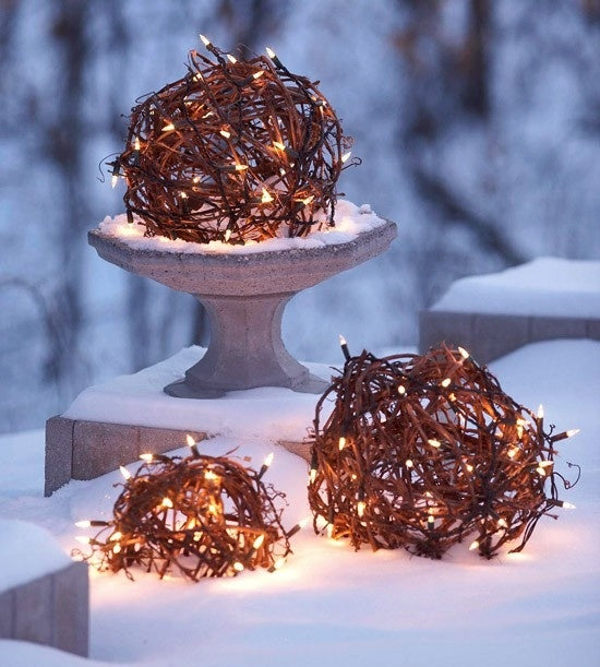 Three round twig tumbleweeds wrapped in fairy lights, sitting on snow