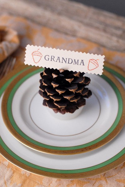 Dinnerware place setting with a pine cone on top and a name tag for grandma
