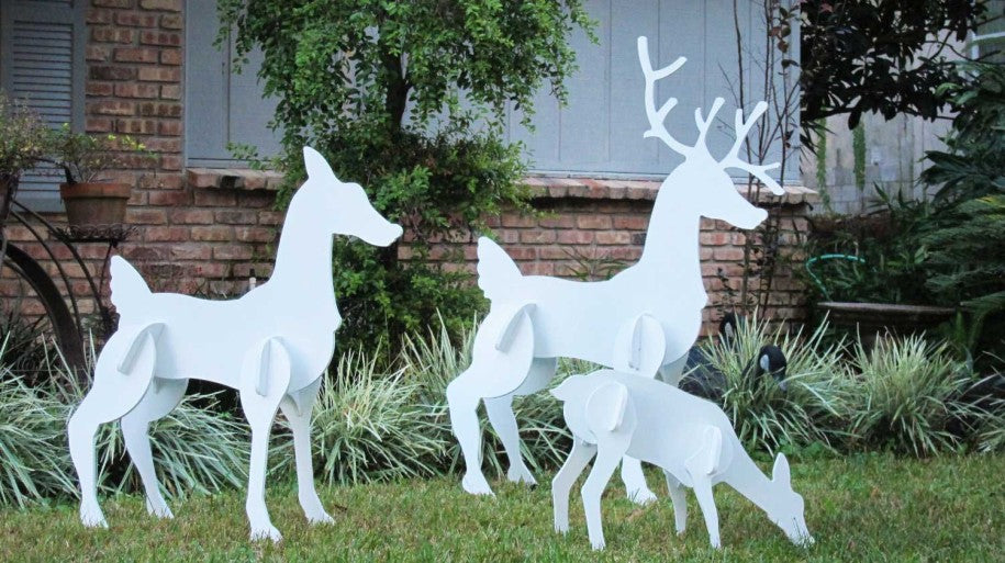 Mummy, daddy and baby deer as white models on a grass lawn